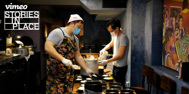 Kitchen workers in face masks preparing bento boxes
