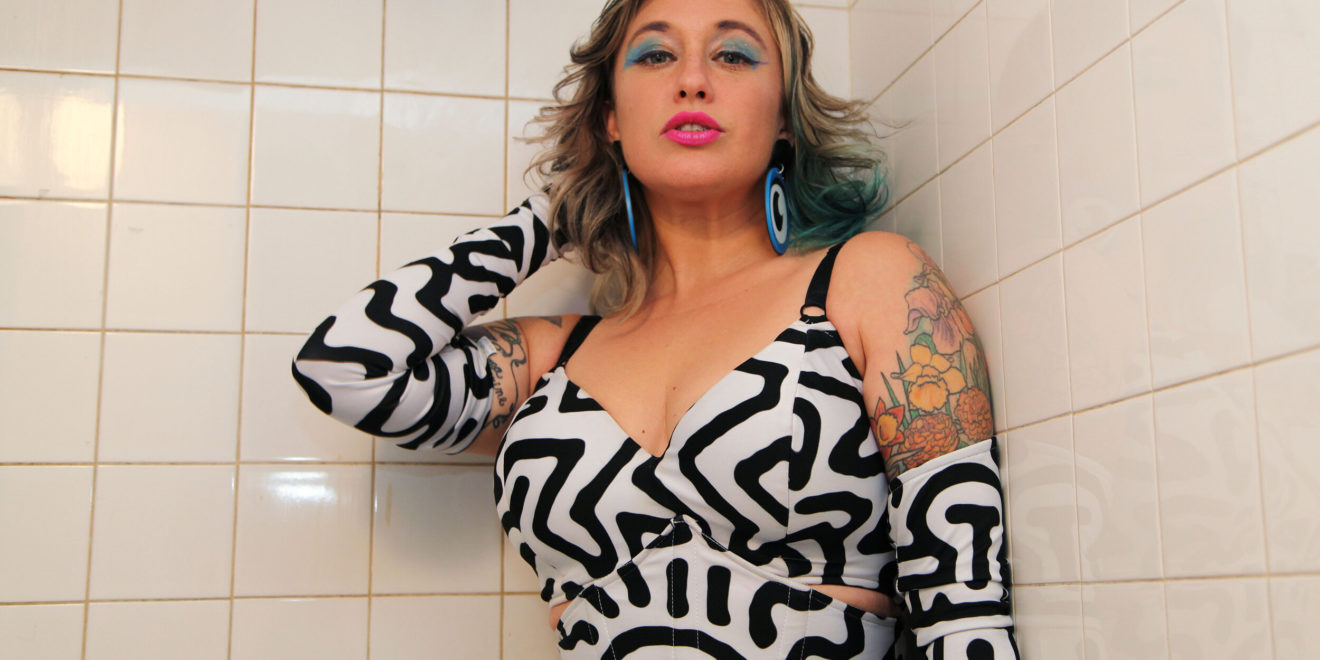 A woman with blue streaks in her hair stands in front of white shower tiles, wearing brightly colored makeup and a Keith Haring-inspired pop art outfit with matching gloves.
