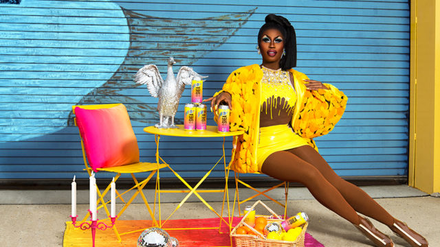 a drag queen in yellow sitting at a bright pink and yellow patio table