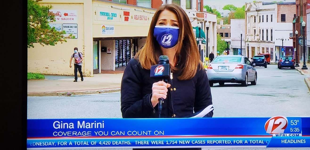 a female news anchor wearing a face mask and talking to a microphone