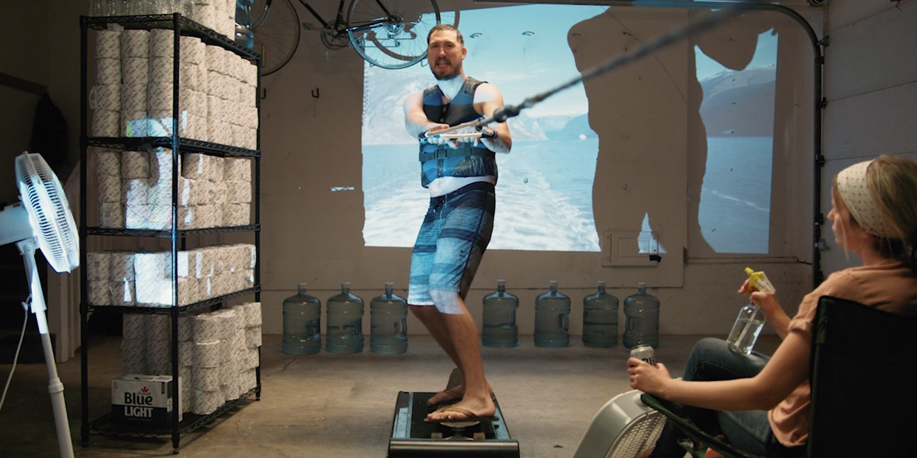 a man pretending to wakeboard in his garage