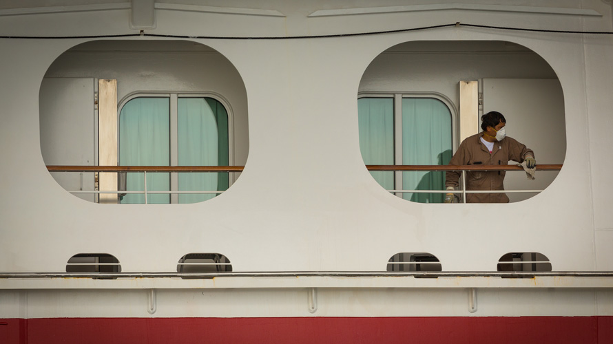 someone cleaning a cruise window while wearing a mask
