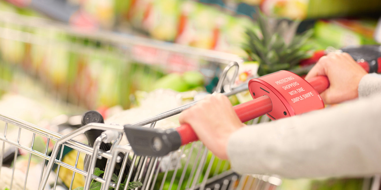 Closeup of a woman's hands pushing a shopping cart filled with healthy food
