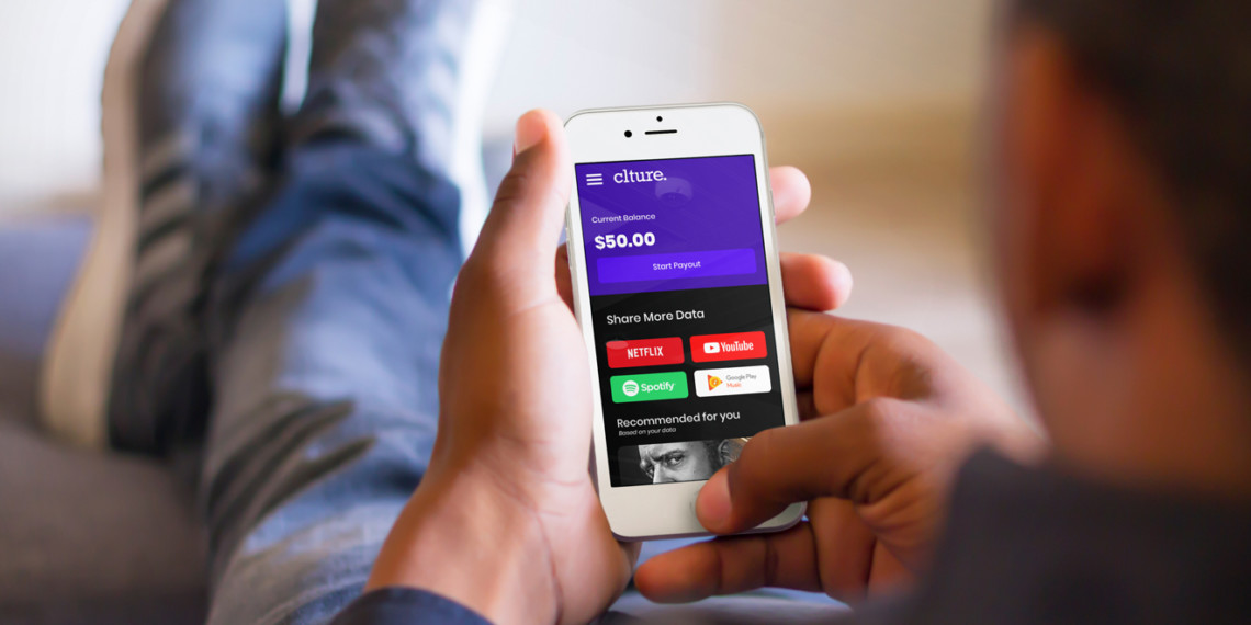 A person holds a cell phone in their hands with the screen showing a $50 balance in the Clture Capital app