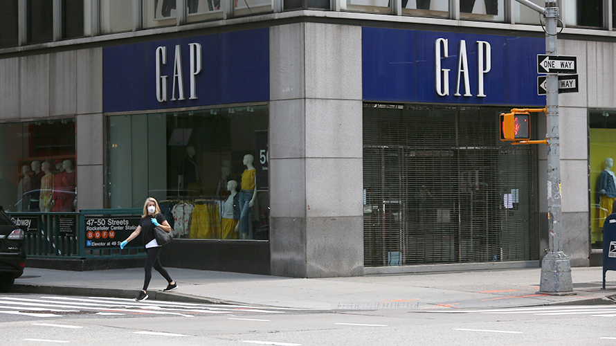 woman wearing face mask and gloves walks past a Gap store in New York City