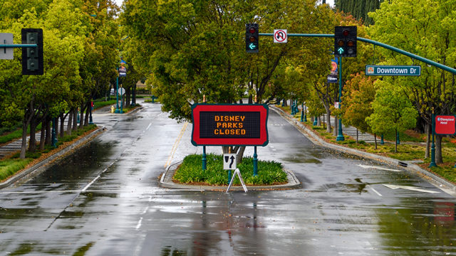 the entrance to an empty disney park with a closed sign