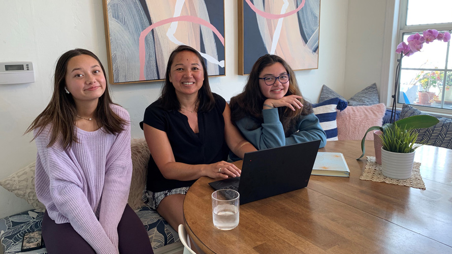 a mother and her two daughters sitting at a table in front of a laptop