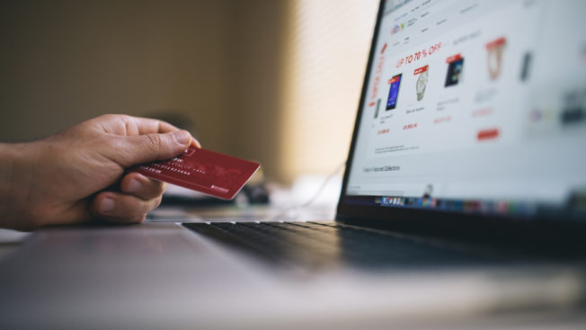 a person holding a credit card sitting at a laptop