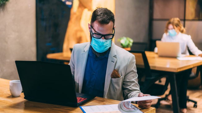Man wearing a face mask in front of a laptop