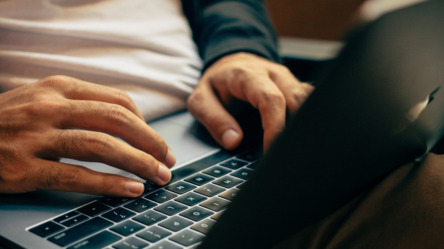 person's hands typing on a laptop