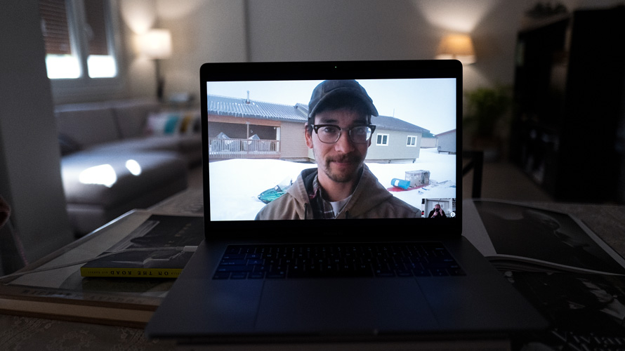 photo of a man wearing a hat and glasses on a laptop
