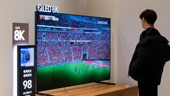 a man watching a giant TV