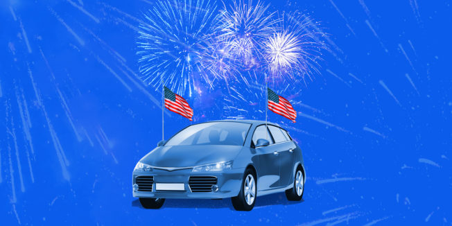 car with American flags and fireworks