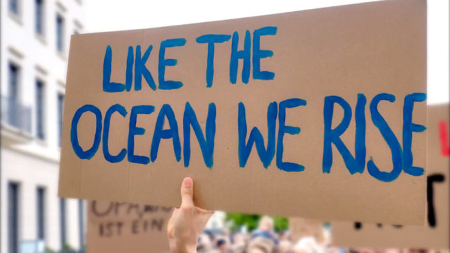 a cardboard sign that says like the ocean we rise