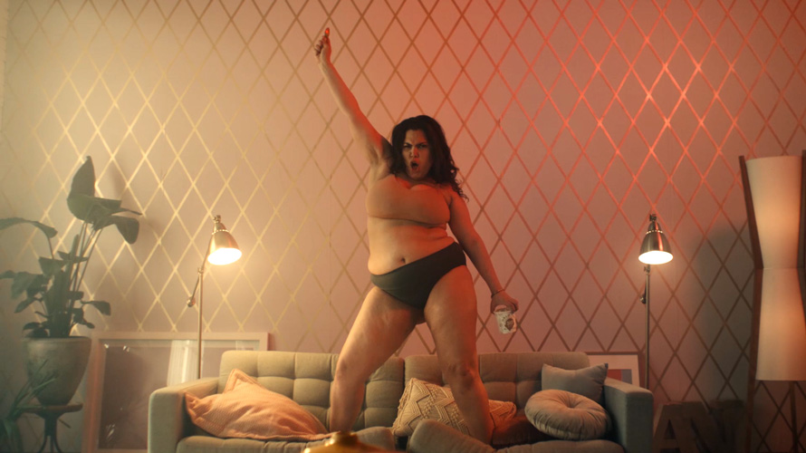 Woman dancing on top of a couch with Halo Top in her hand