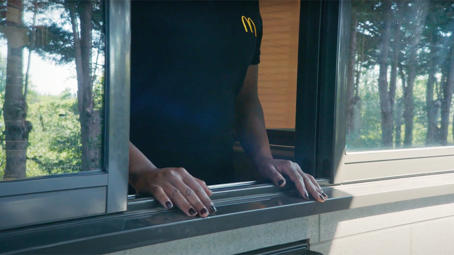 Image of a McDonald's drive-thru worker at a window