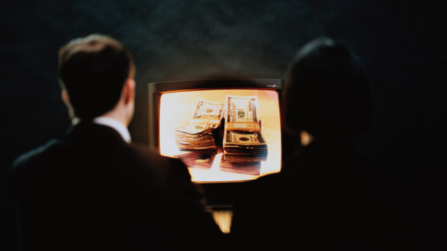 two people staring at a tv screen with money on it
