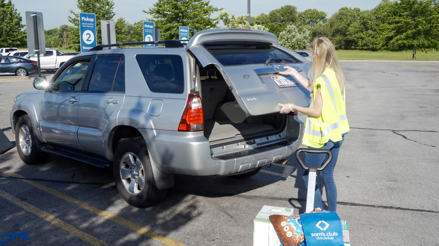 a woman opening the trunk of a car