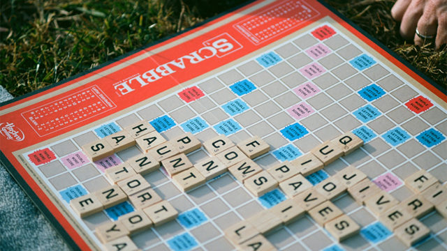 Close-up of Milton Bradley Scrabble game board in a grassy, park setting