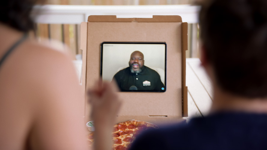 Screenshot of Shaquille O'Neal talking on a video placed inside of a pizza box
