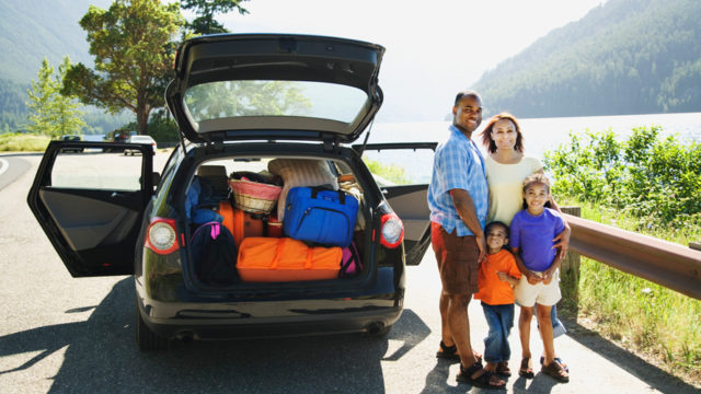 Family standing next to a packed car
