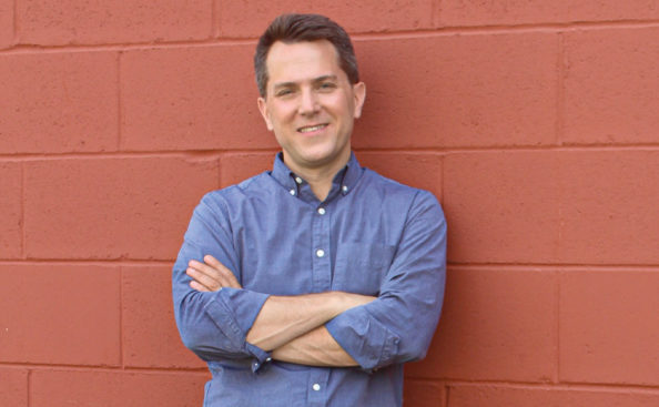 a man standing in front of a red wall with his arms folded