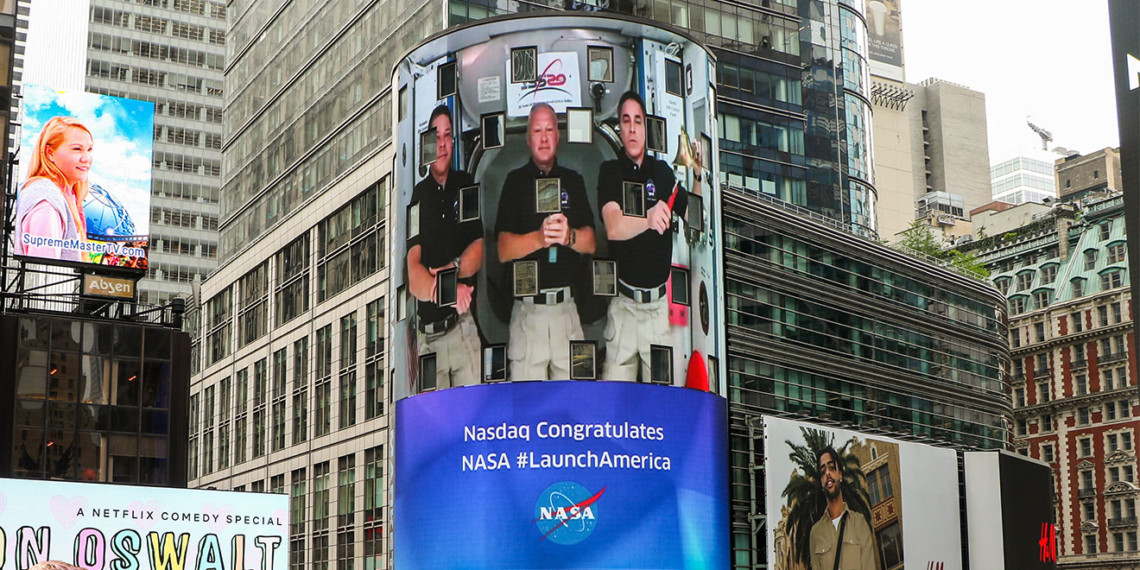 Astronauts Bob Behnken, Doug Hurley and Chris Cassidy on a giant LED screen
