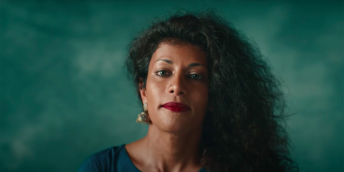 a black woman with curly hair on a dark green background