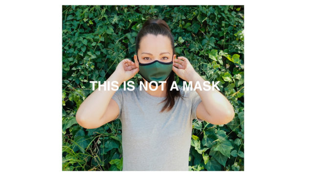 A woman wearing a mask with text that says, 'This is not a mask'