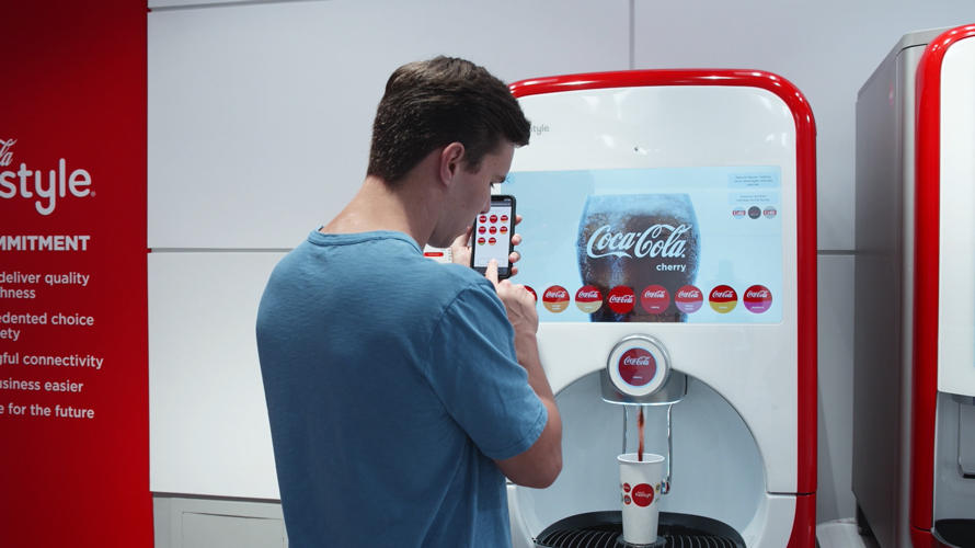 a man using his phone to select a coke from a coke vending machine