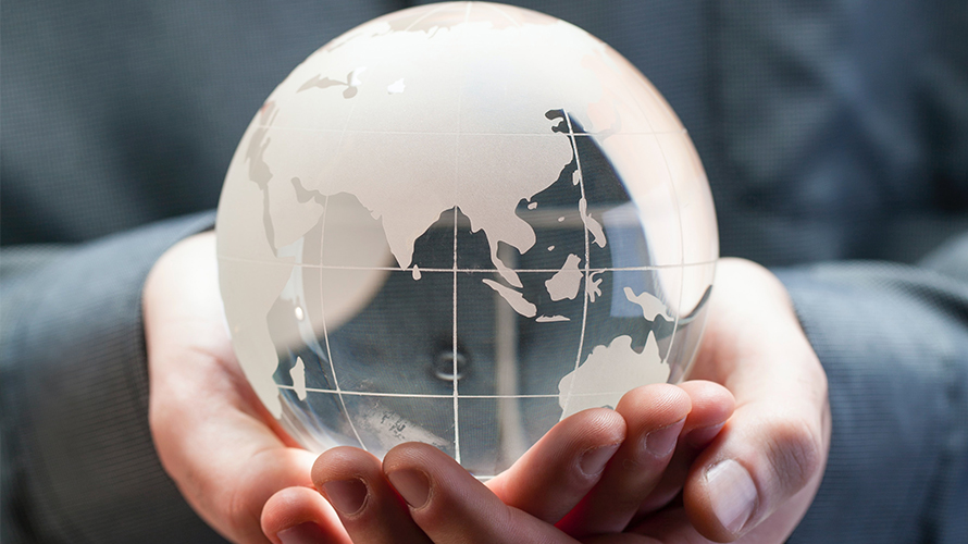 Person holding glass world globe in hands