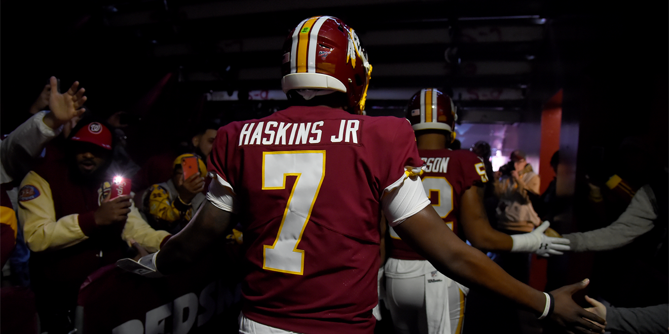 a man in a red football jersey number 7 that says haskins jr