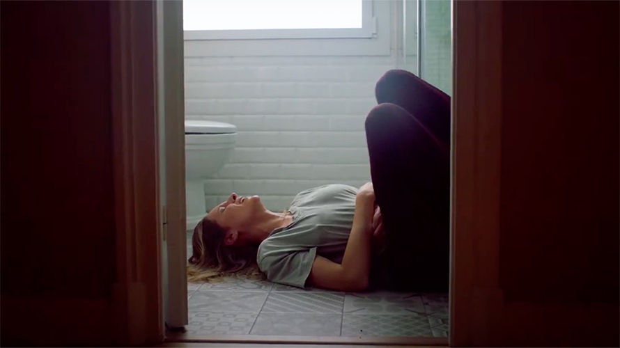 a woman lying on a bathroom floor crying, gripping her stomach