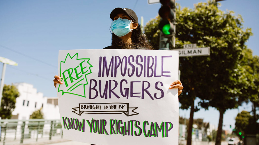 Woman holding up sign for Impossible burgers