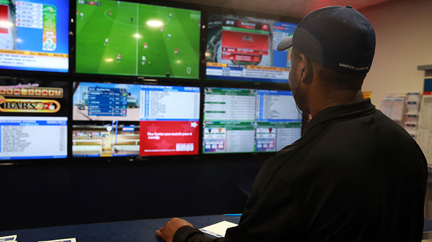 a man wearing a hat looking at six different video game screens