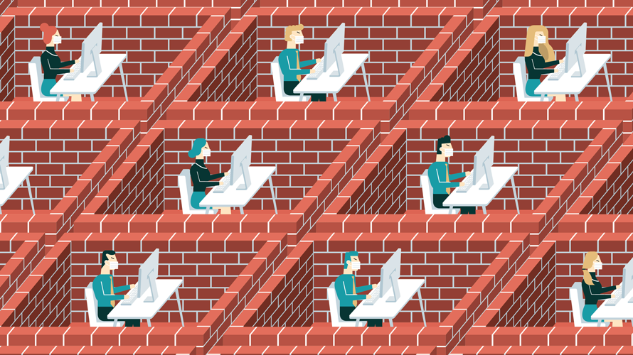 people sitting in bricked-in cubicles