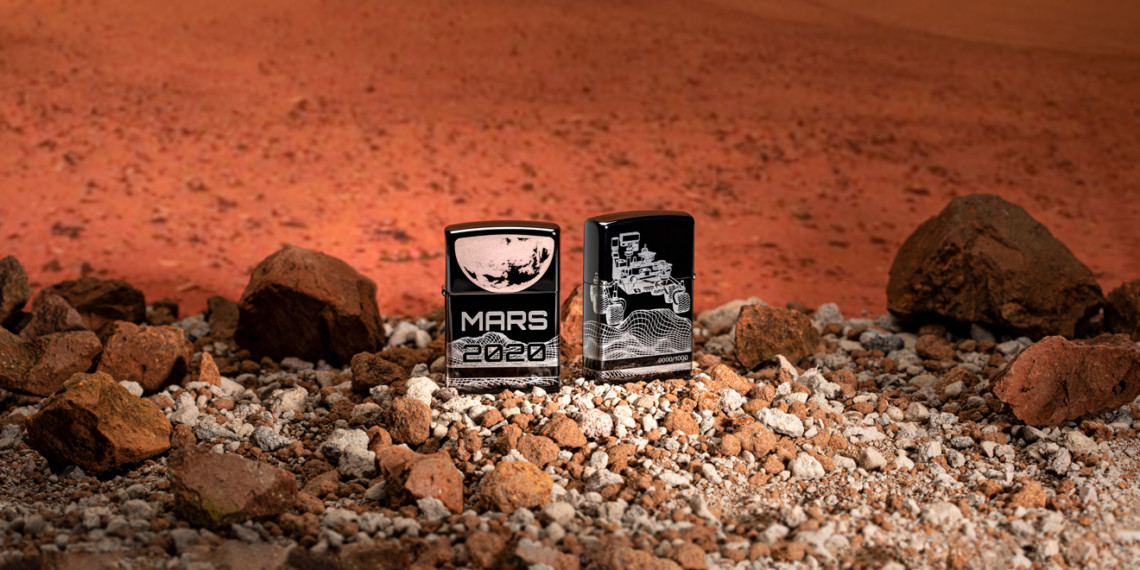 two black zippo lighters on rocks with engravings of space on them
