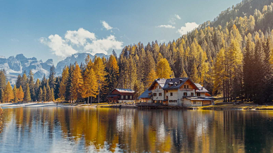 a picturesque view on a home on a lake amid trees and mountains