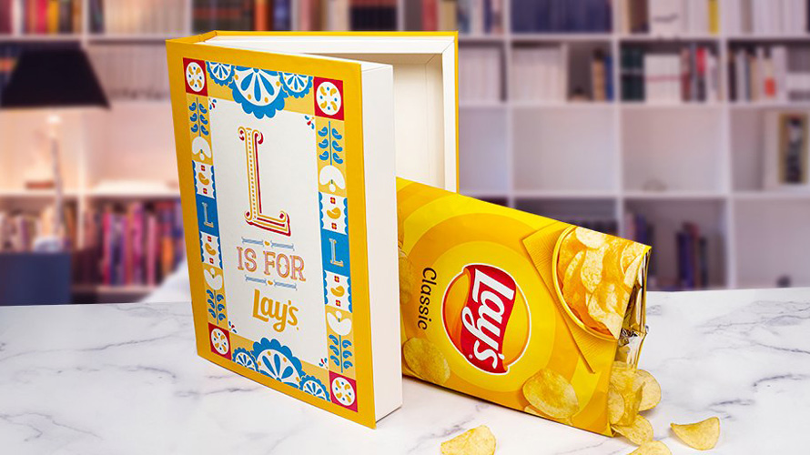 a lay's chip bag falling out of an open hollowed out book
