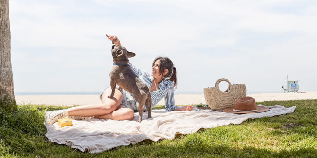 a woman on a blanket in a park with her dog
