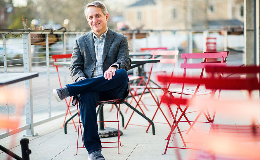 a man sitting on a red folding chair outside