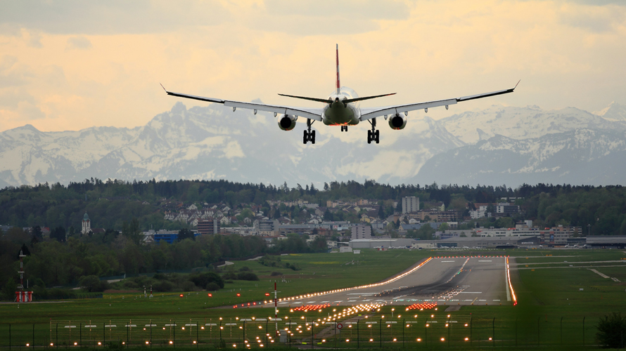 Airplane landing with mountains in the distance