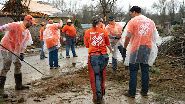 people in home depot shirts working to clean up after a natural disaster