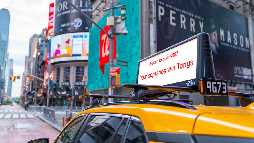 """a cab driving through the city with an ad on top that says """"reason to smile #187: your sopranos win tonys."""""""