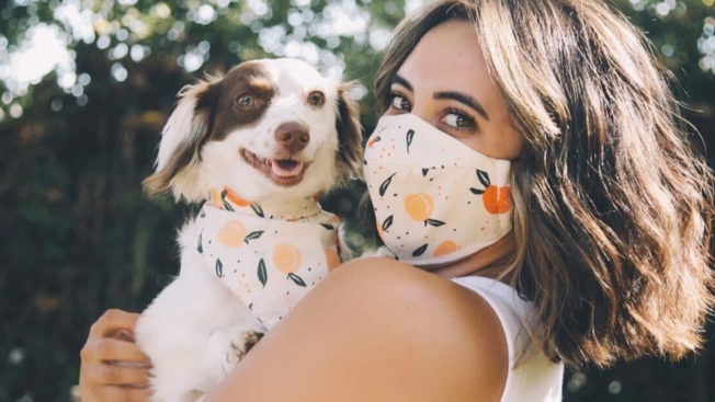 Photo of a woman in a face mask holding a dog