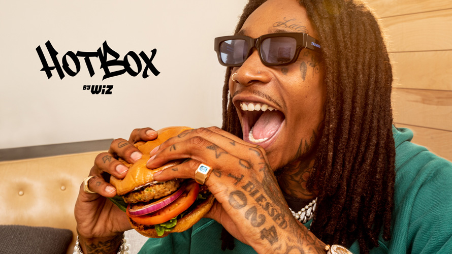 wiz khalifa eating a burger next to text that says hotbox by wiz