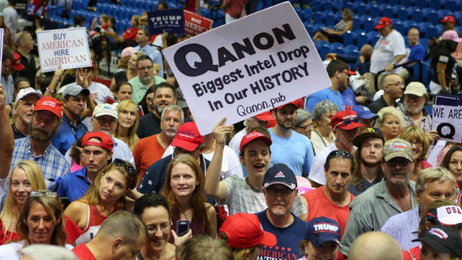 crowd with people holding QAnon signs