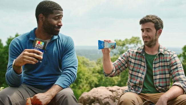 two men sitting outdoors, one on the left eating a kind bar and the one on the right looking skeptically at a clif bar