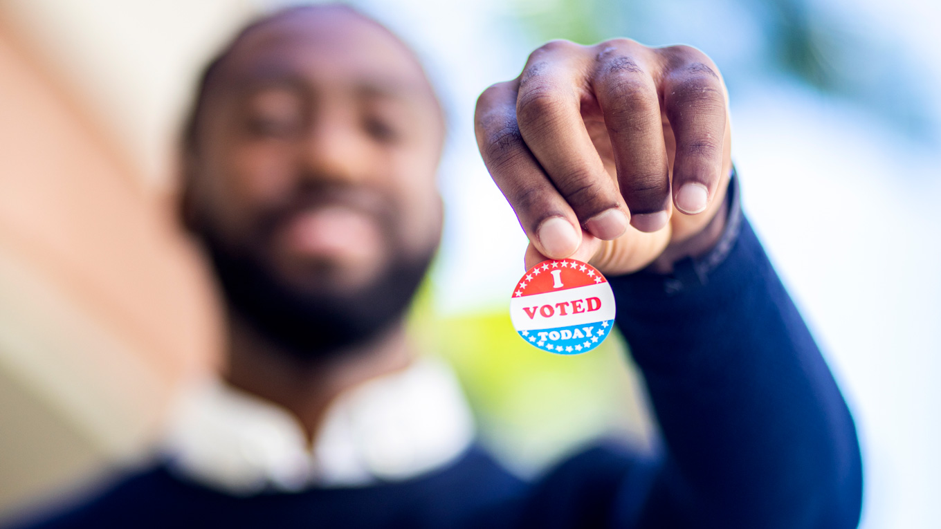 a man holding up an i voted sitcker