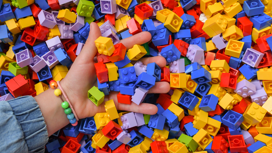 a hand dipping into a pile of lego blocks